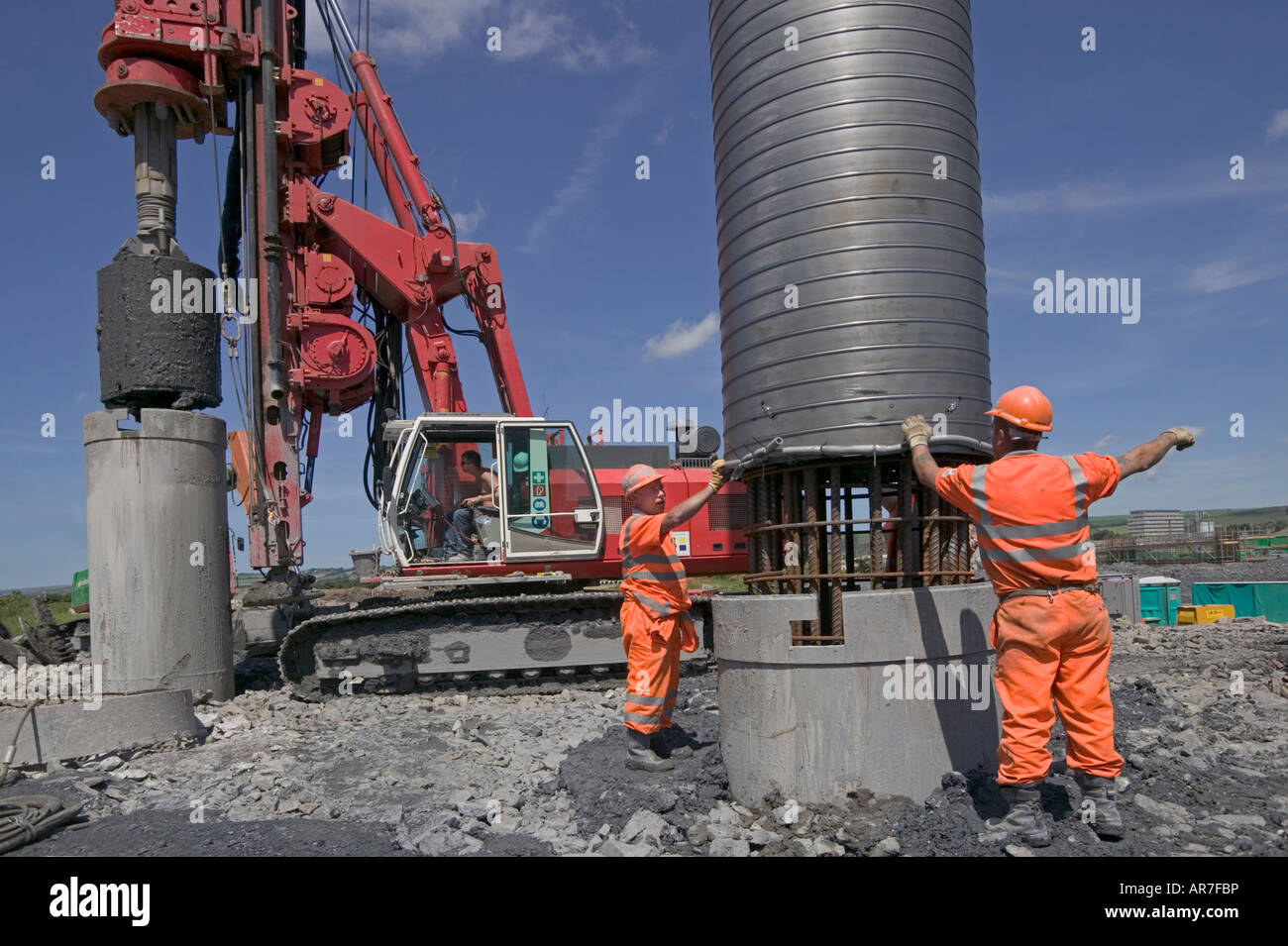 Workers install steel reinforced cage into excavated pile. In the background, a massive piling rig lifts spoil from - Stock Image
