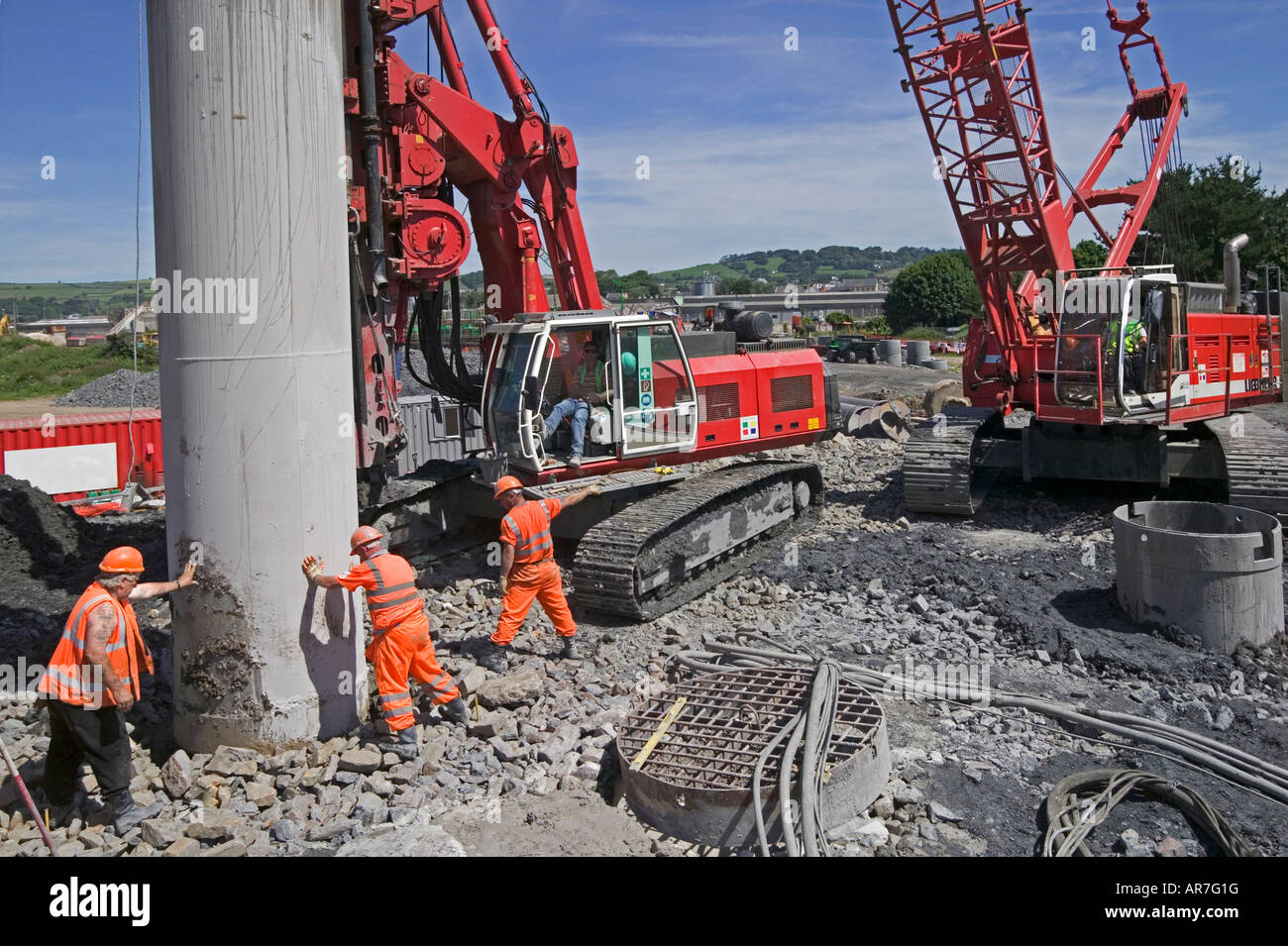 Workers install temporary piling support casing. A network of reinforced piles provides a foundation for a heavy - Stock Image