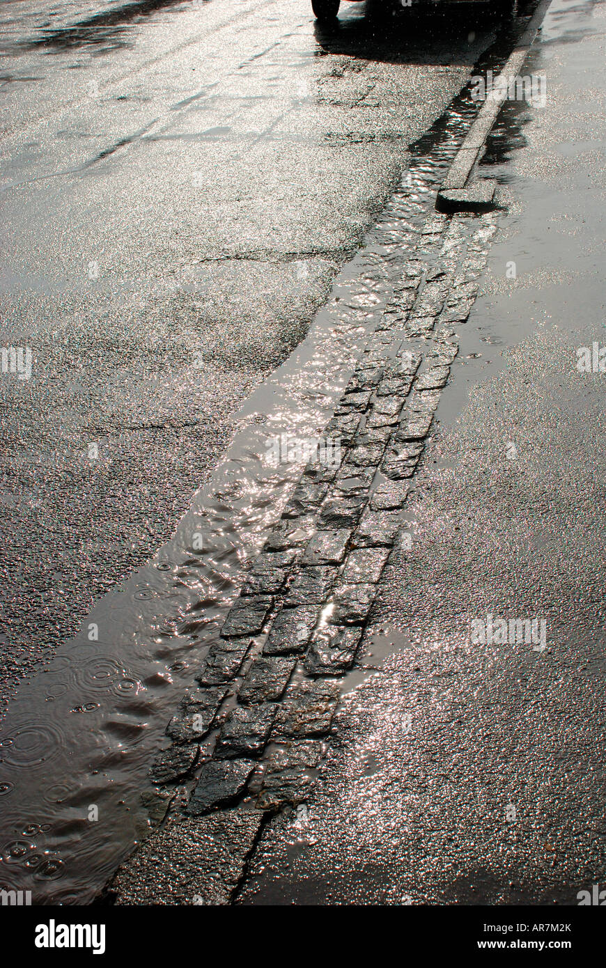 Rain On Street With Water Flowing In Gutter Stock Photo Alamy