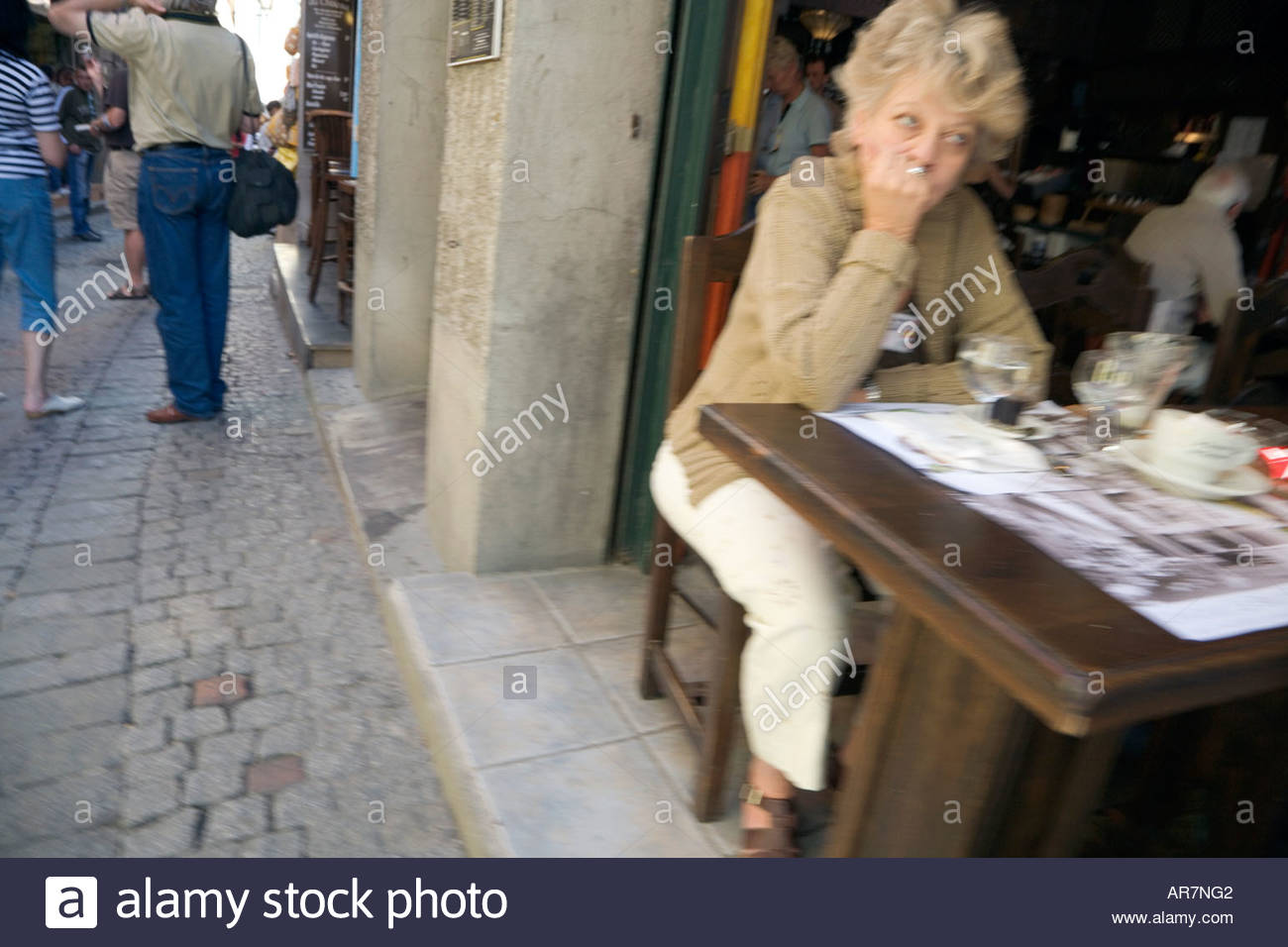 middle aged woman sitting at a restaurant waiting - Stock Image
