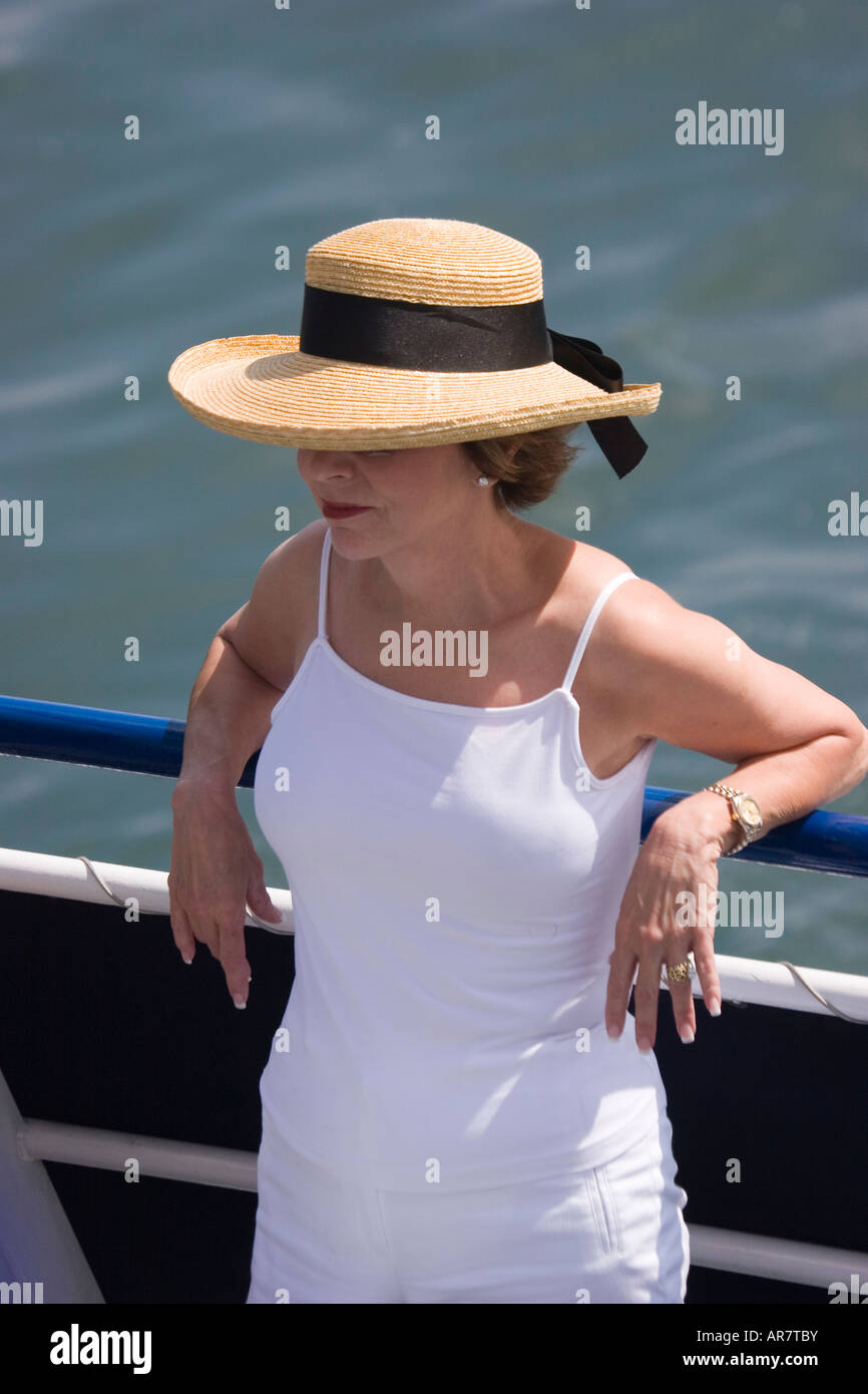 A woman wearing a straw hat relaxes against the railing of a ship on a warm and sunny day. Stock Photo