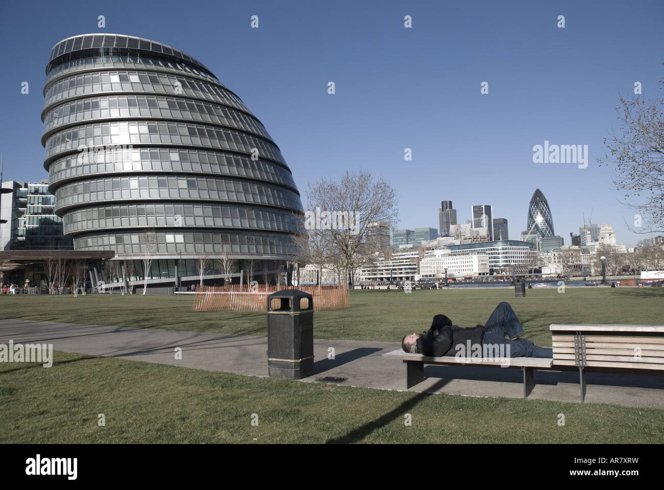 London Assembly with homeless person in foreground and St Mary Axe Gherkin in background - Stock Image
