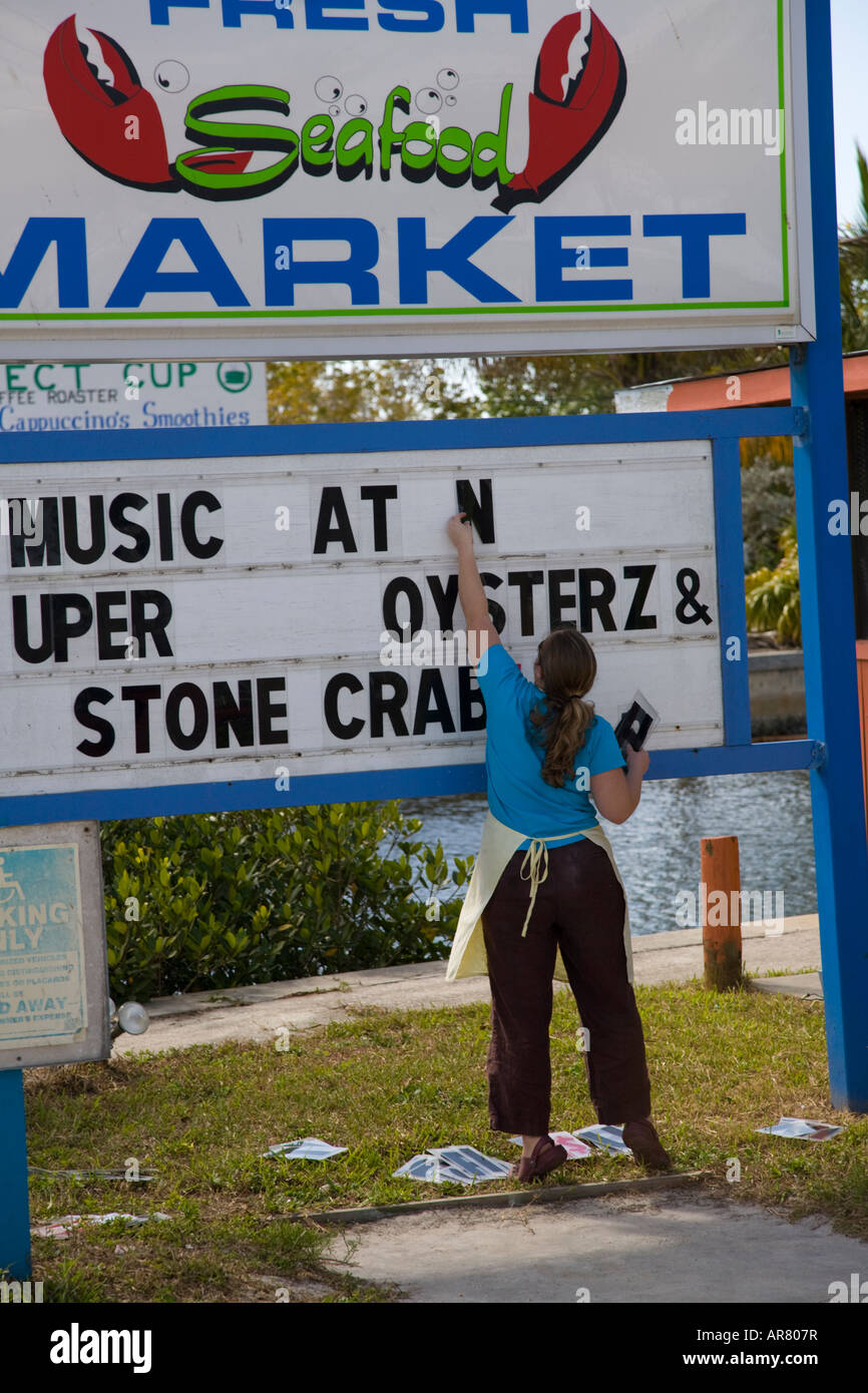 Woman changing sign board at seafood market in Matlacha Florida on the southwestern Gulf Coast of Florida - Stock Image