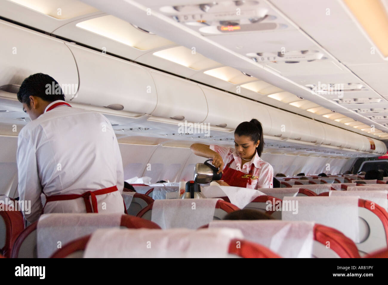 Air hostess serves coffee on a flight in India - Stock Image