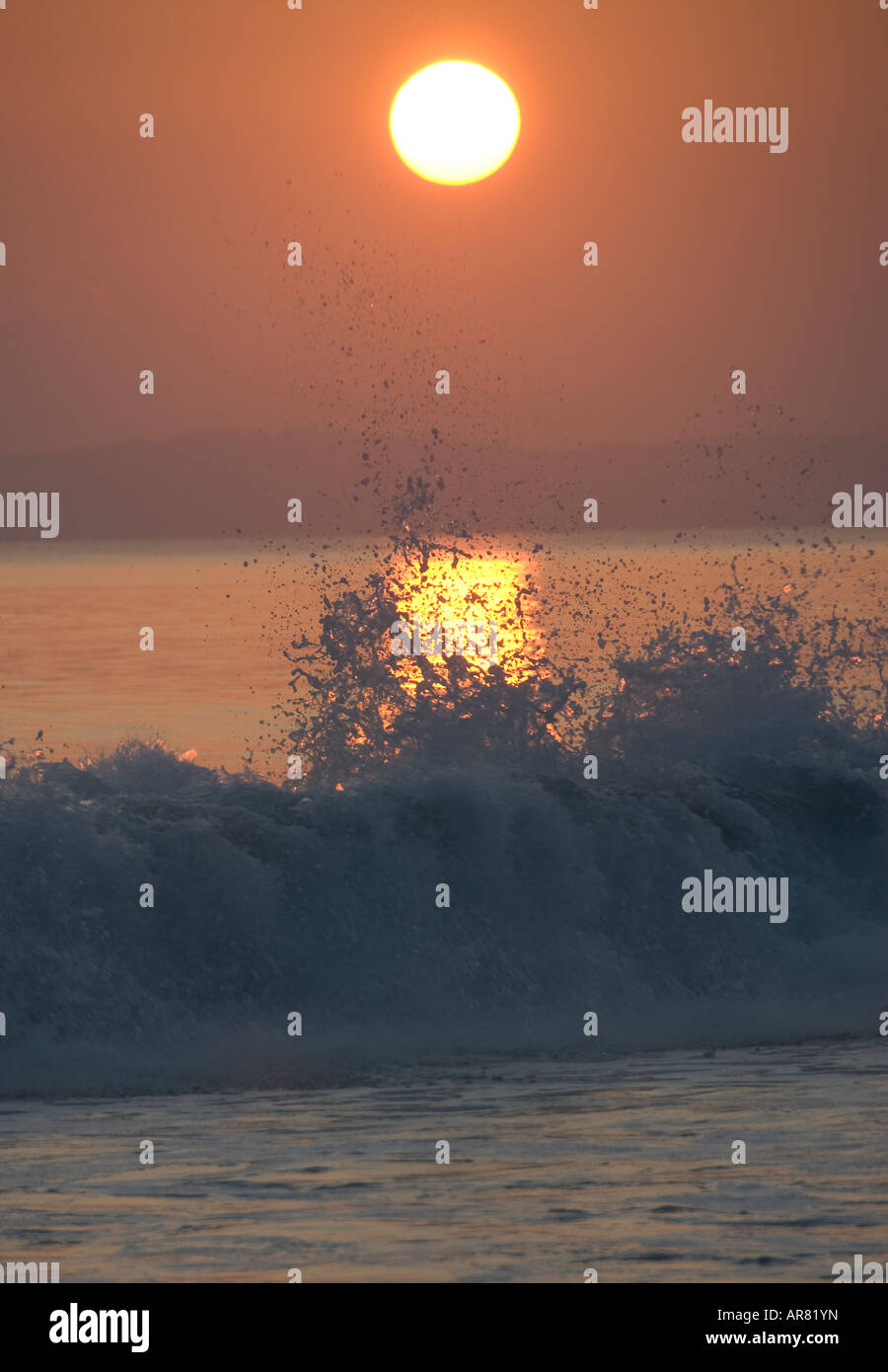 Sunset and wave breaking - Stock Image