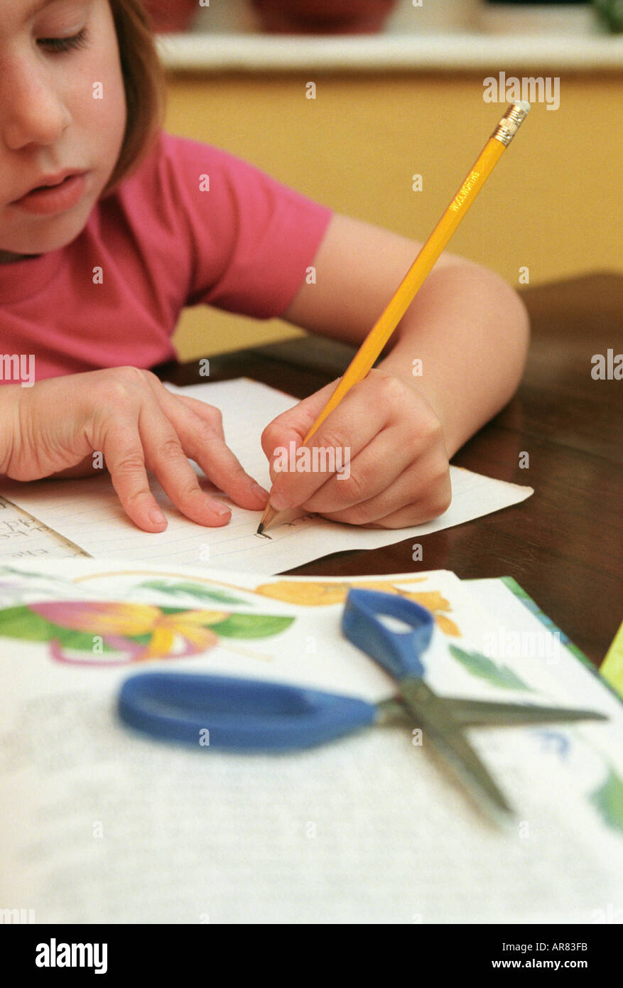 Young girl writing with her left hand - Stock Image