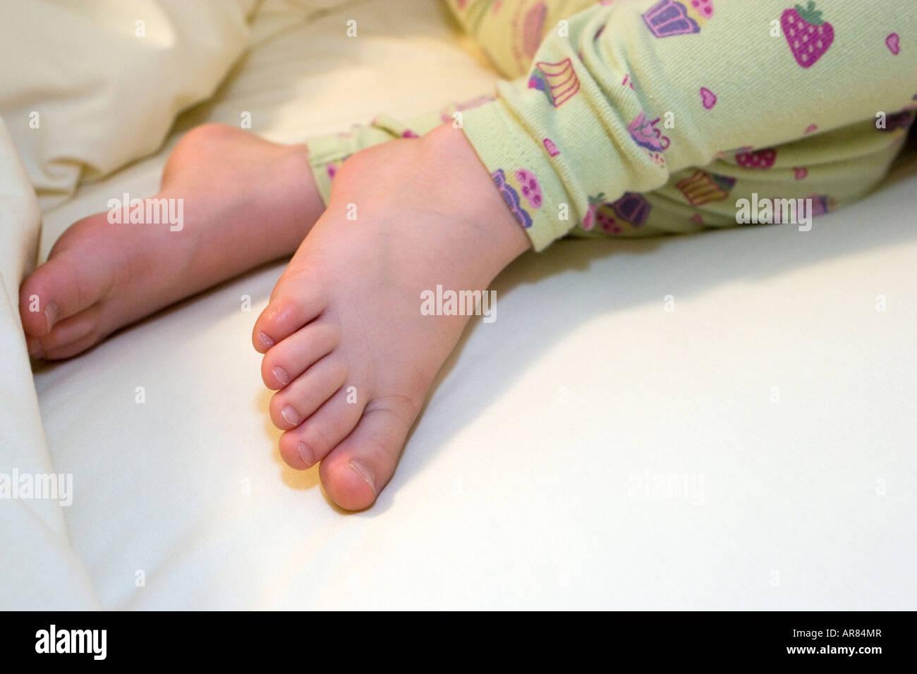 Understood little girl sleeping in bed feet