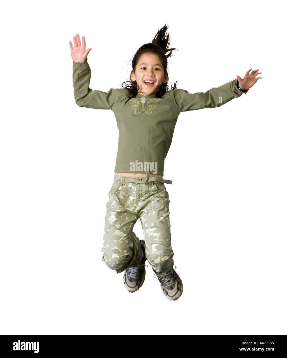 Preteen Latino girl jumping for joy - Stock Image