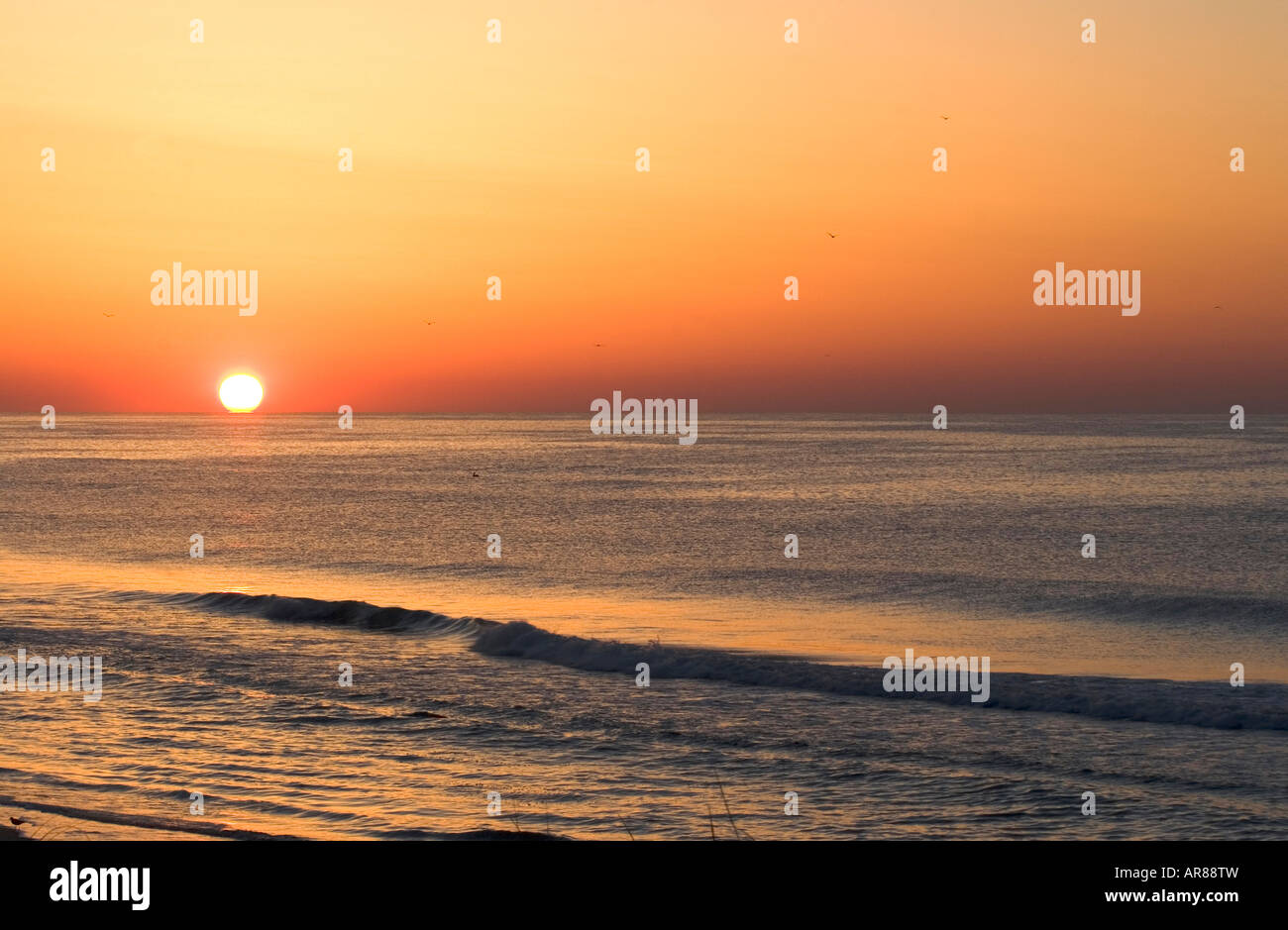 Waves drift toward shore as the sun rises over the Atlantic Ocean where beneficial negative ions outnumber positive - Stock Image