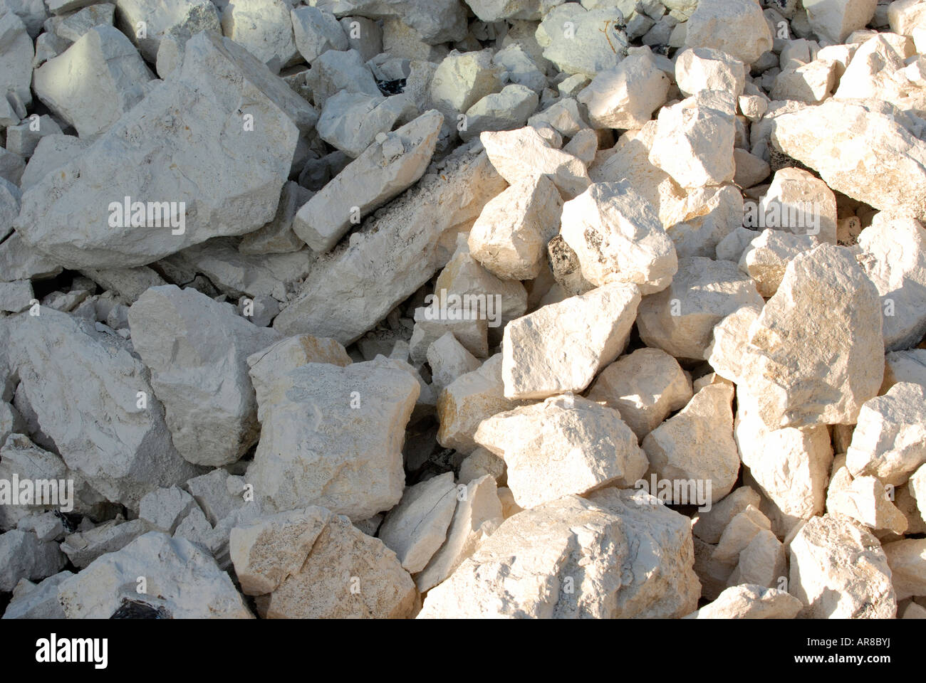 boulders stones of chalk rocks hardcore white in colour in a pile making a decorative background for text in sunlight - Stock Image