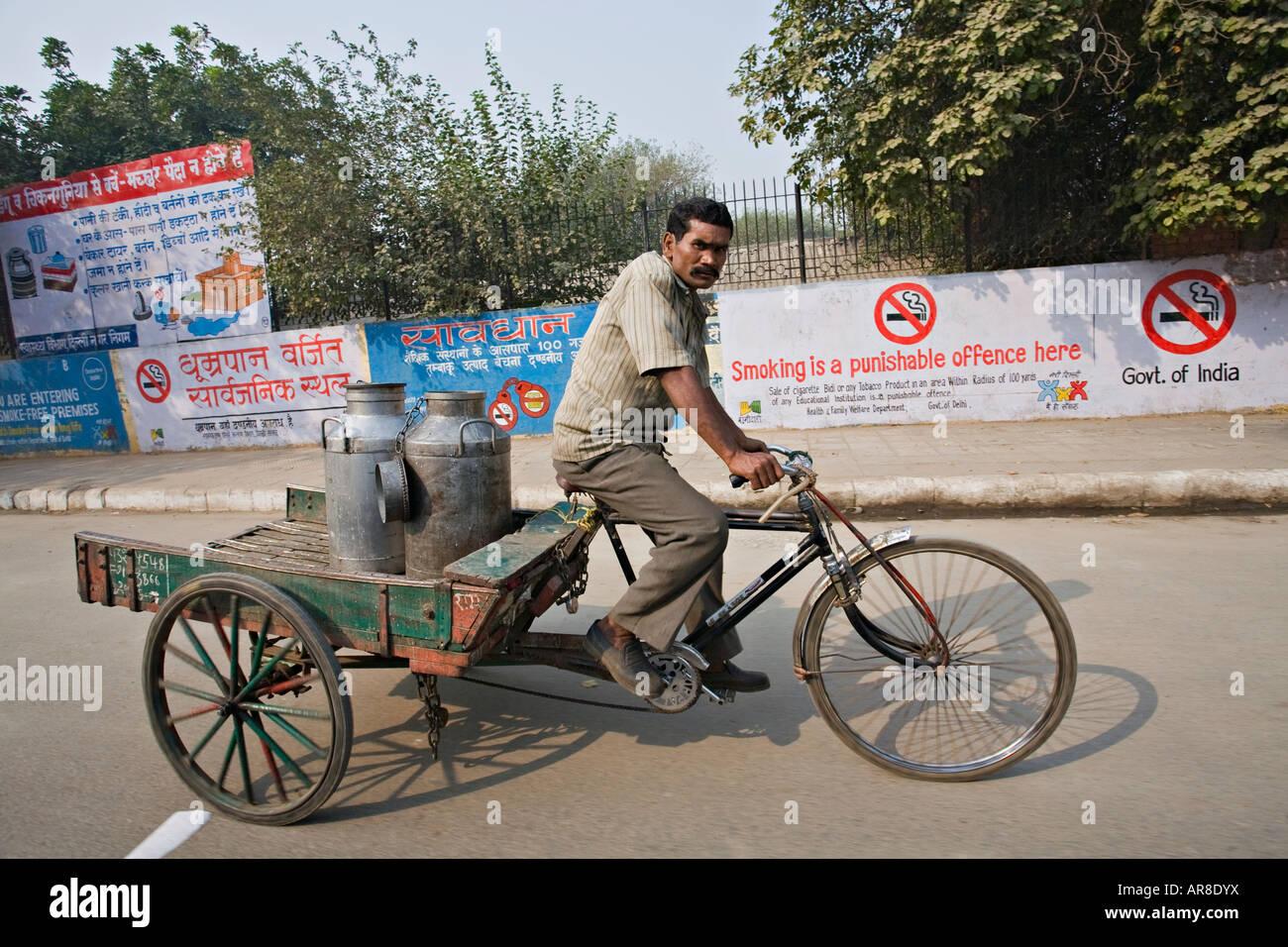 Indian man selling milk on a bicycle, Netagi Subhash Marg, Delhi, India - Stock Image