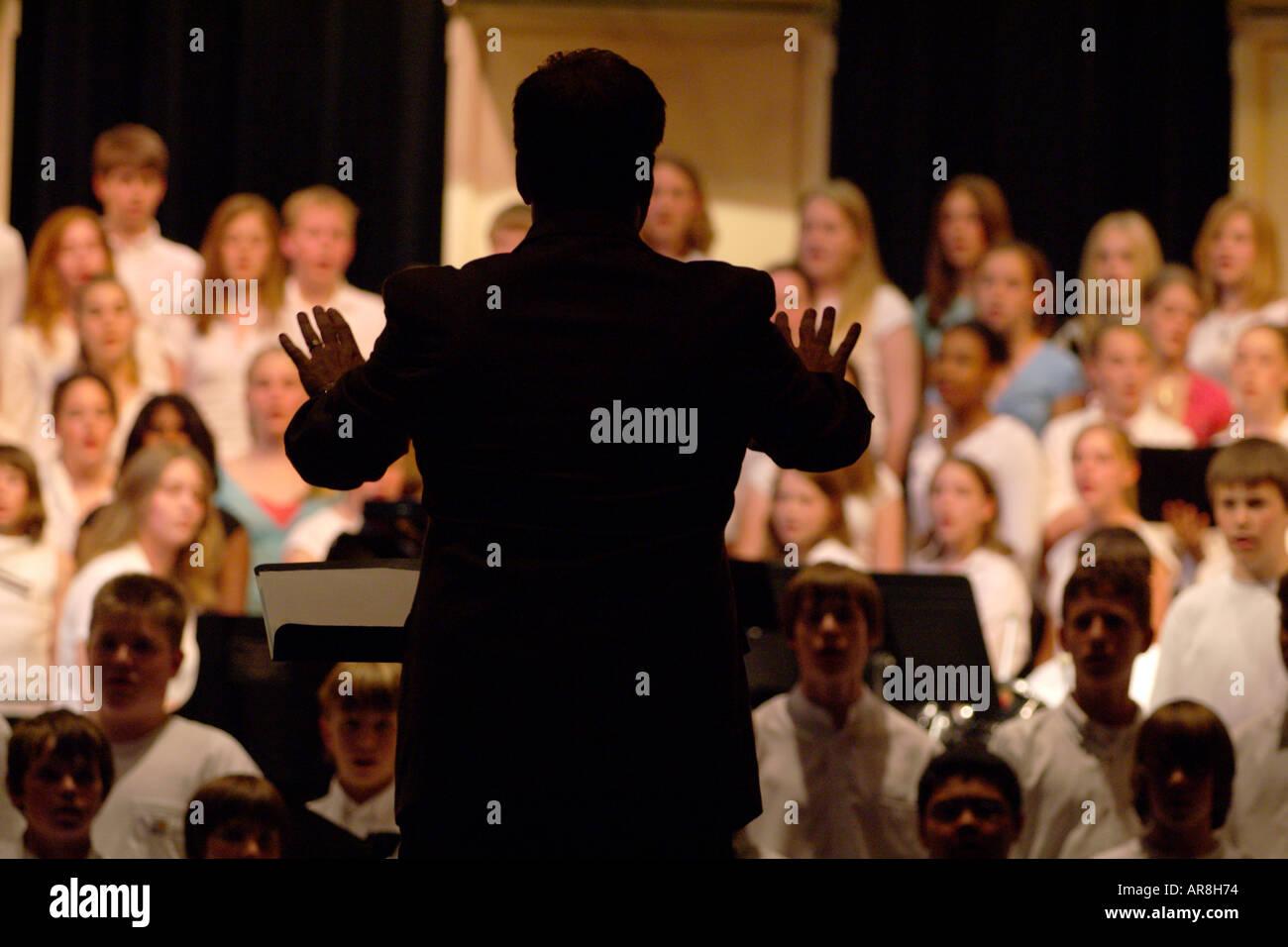 choir director directing teenage singers - Stock Image
