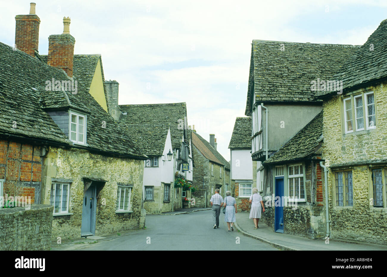 Lacock village in Wilshire, England. Visitors walk down street of old houses toward public house called Sign of the Angel. - Stock Image