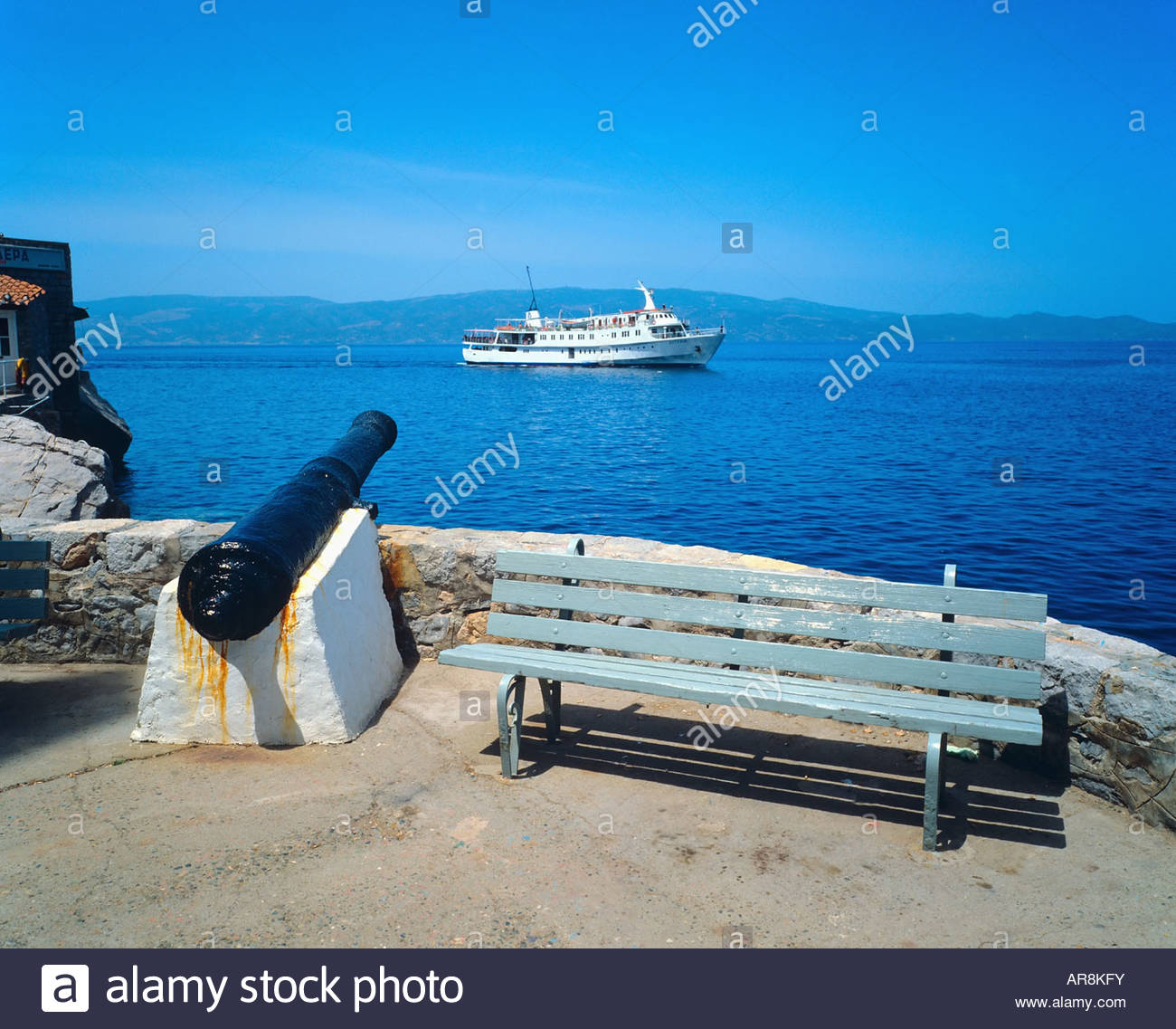ANCIENT FORTIFICATION AND CRUISE SHIP HYDRA ISLAND SARONIC GULF GREECE - Stock Image