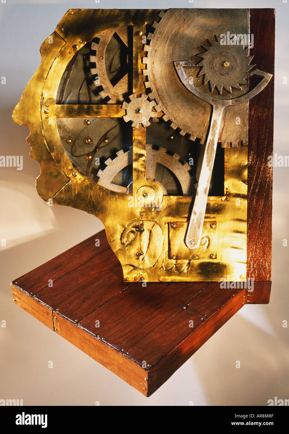 Metal face face made of clock mechanisms, interlocking cogs and levers turning, standing on wooden base, face in profile. - Stock Image