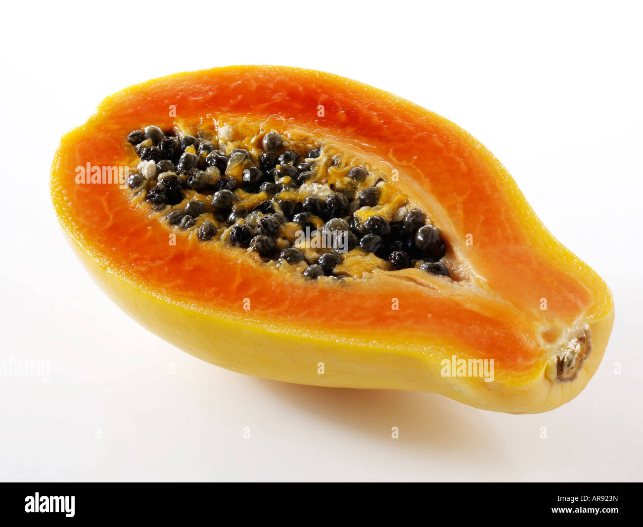 papaya tropical fruit cut in half against a white background as a cut out - Stock Image