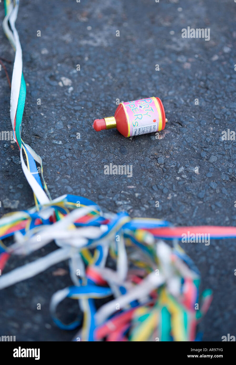 Used 'Party popper' in the road the day after a party - Stock Image