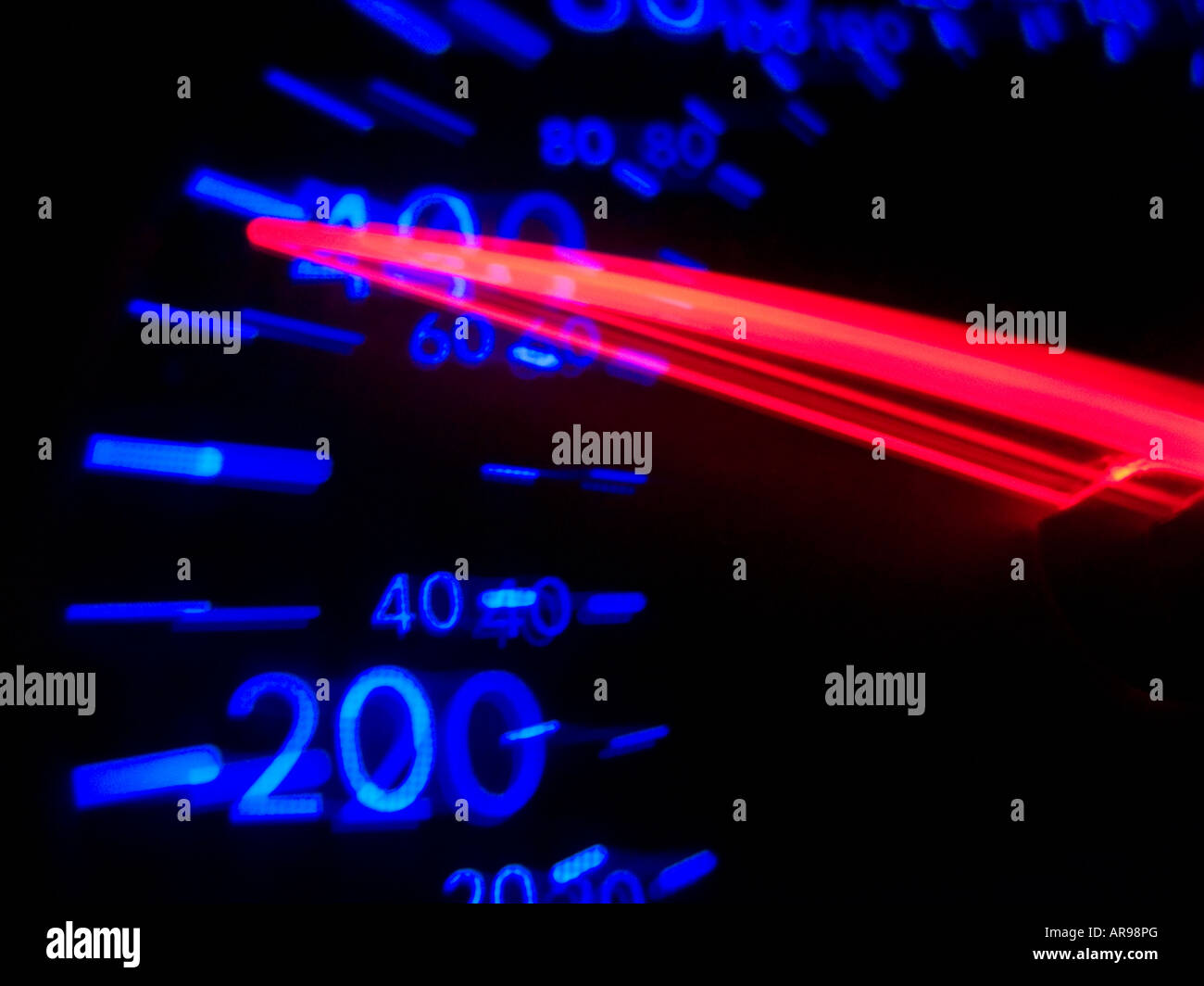 Blurry speedometer odometer car dashboard illuminated at night - Stock Image