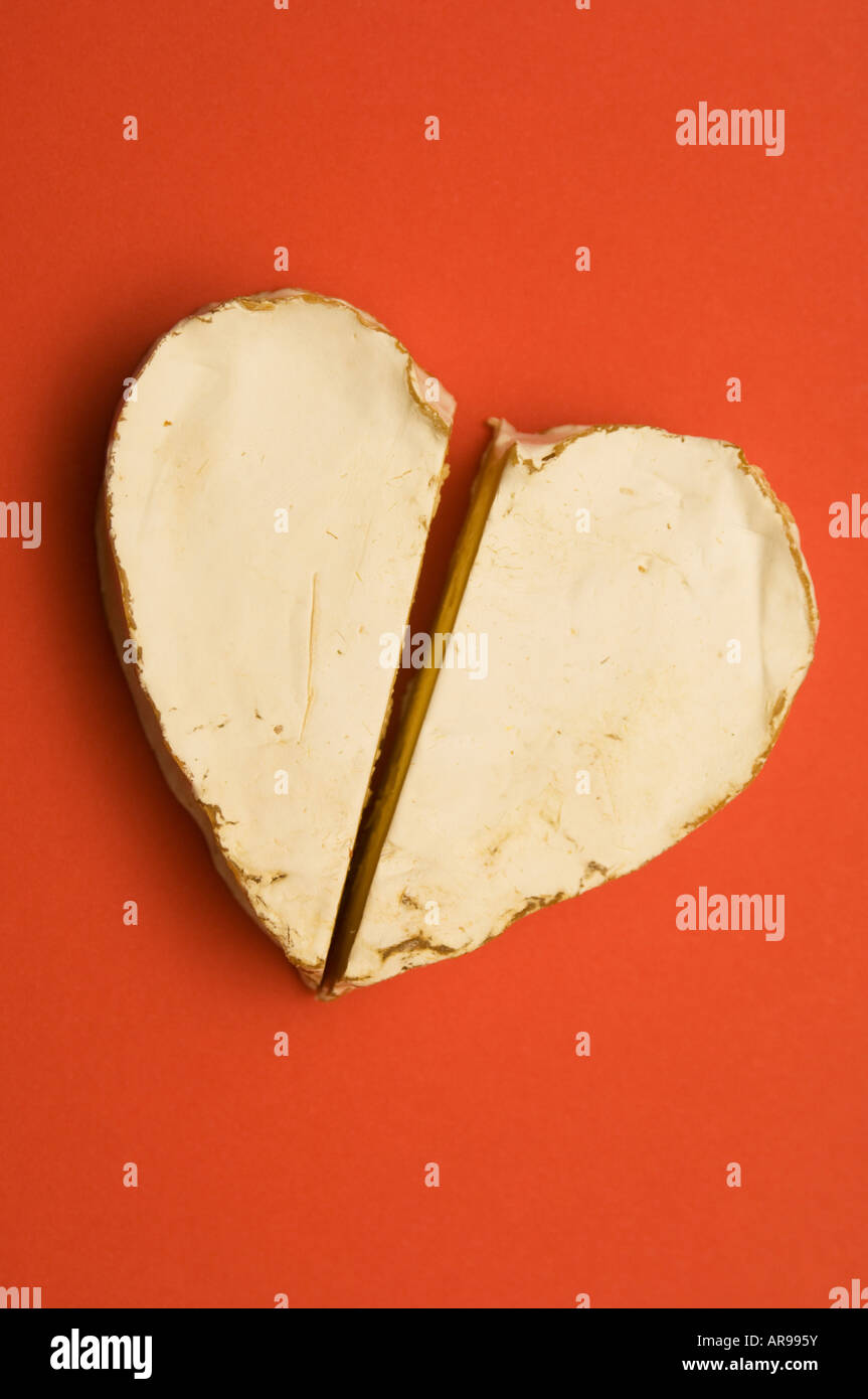 cheese coeur de neufchatel french heart romance romantic shape soft valentine red background food cut half halved - Stock Image