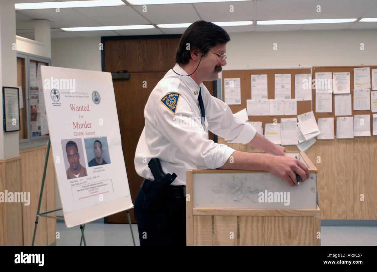 Police Desk Sergeant conducting role call - Stock Image