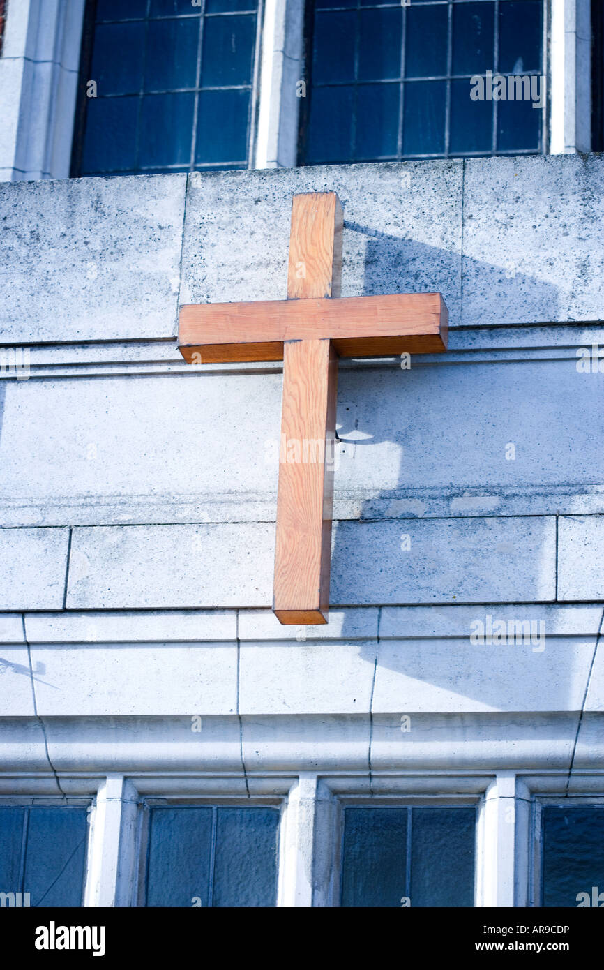Cross hanging on the side of a building UK - Stock Image