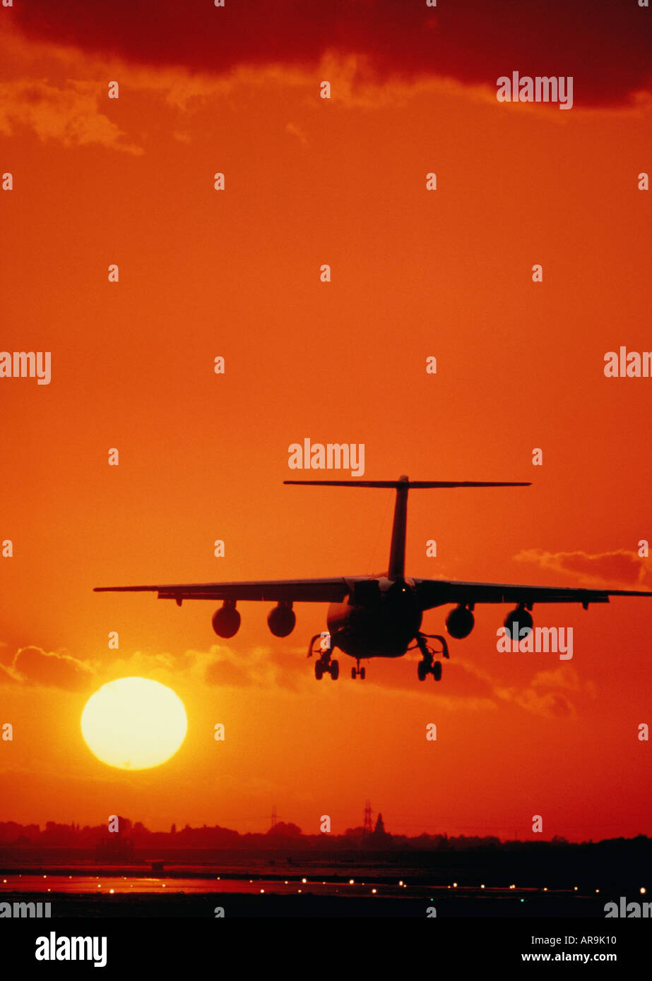 BAE Avro Regional Jet RJ 146 flying runway lights heading into an golden orange sky at sunset sunrise dusk showing jet - Stock Image