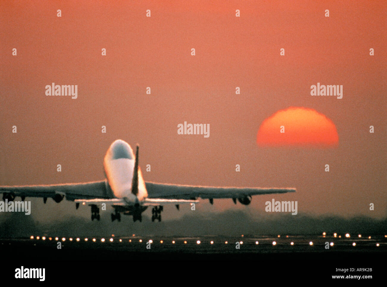 airliner Boeing 747 jumbo jet airliner taking off at sunset sunrise dusk showing jet thrust exhaust - Stock Image