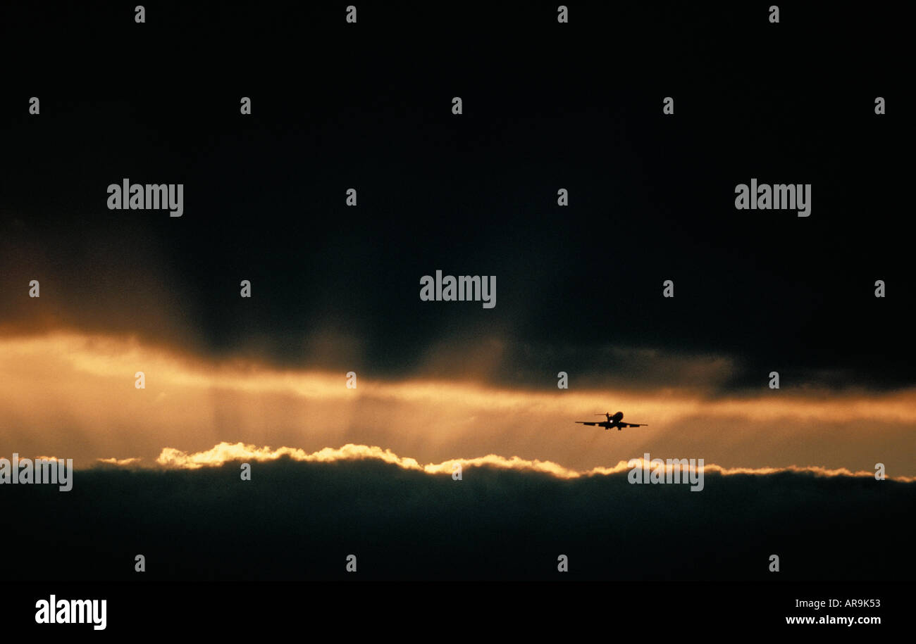 Boeing jet airliner flying in dark cloudy sky at sunset - Stock Image