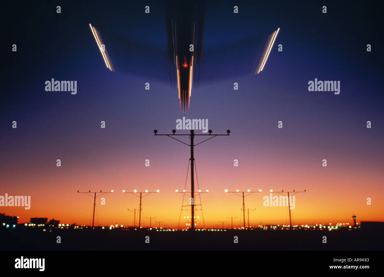 airliner landing over runway approach lights at night dusk sunset sunrise - Stock Image
