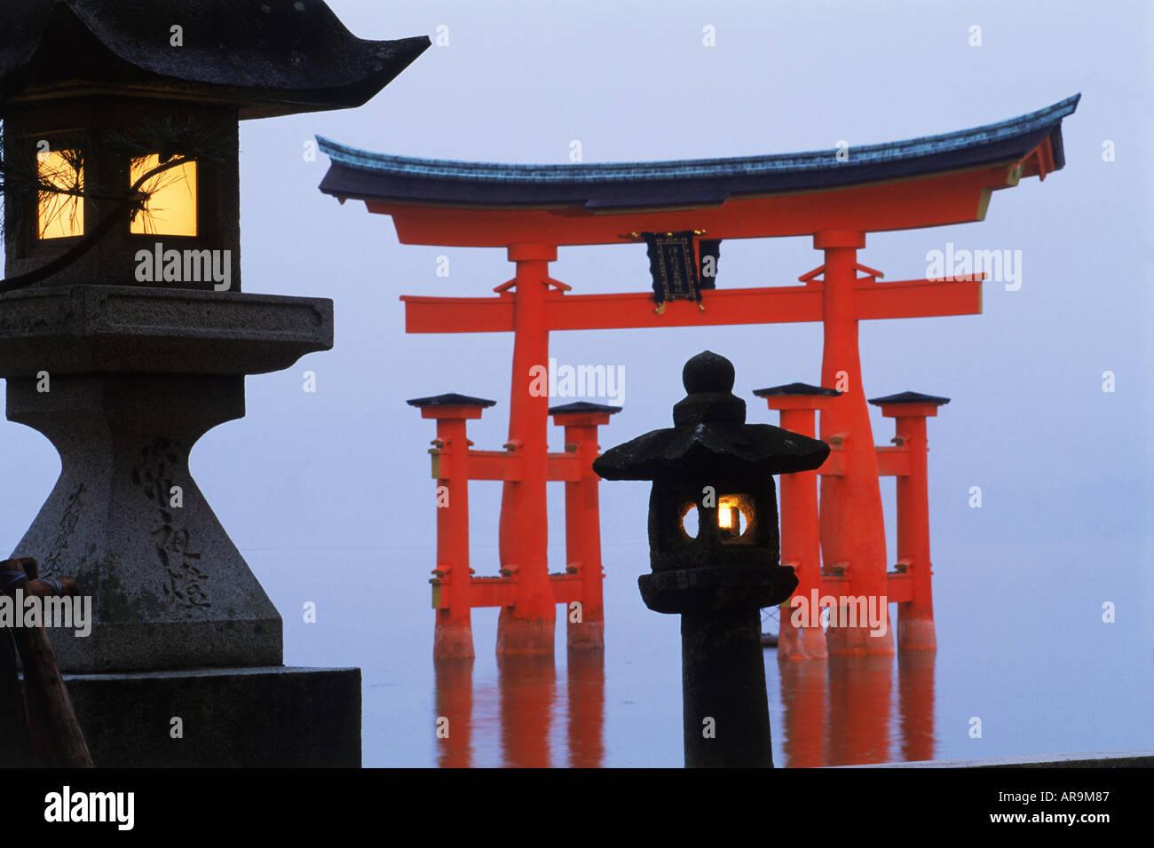 Itsukushima Torii (temple gate) in the sea in misty twilight on Miyajima Island. Japan - Stock Image
