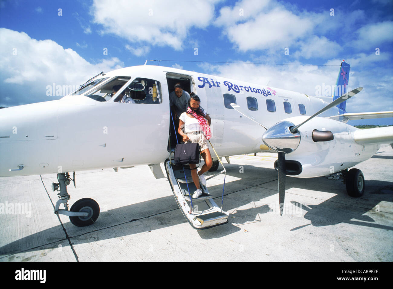 Tourists in Cook Islands exiting inter island flight - Stock Image