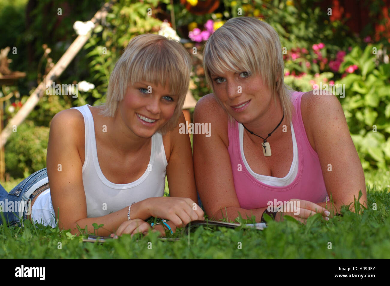 junge Mädchen mit Zeitschrift | young girls lying in the grass with a magazine Stock Photo