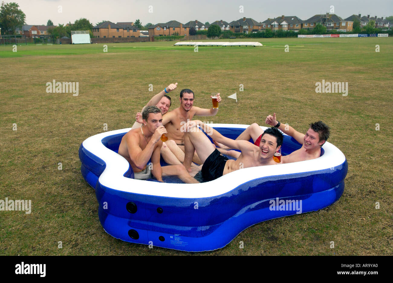 Team members at Keynsham Cricket Club near Bristol England UK relax with beer in a paddling pool when rain stopped play - Stock Image