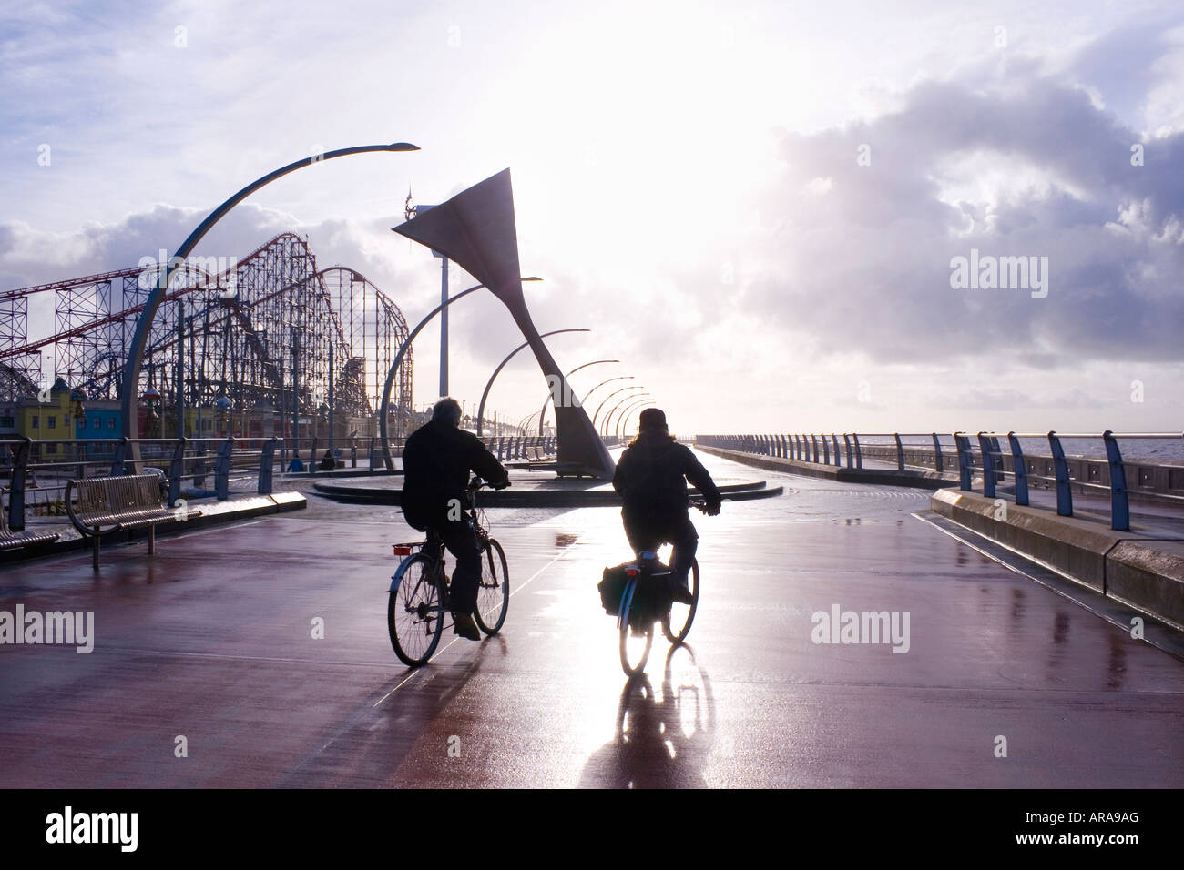 Blackpool England Two cyclists passing Swivelling Wind Shelter Sculpture - Stock Image