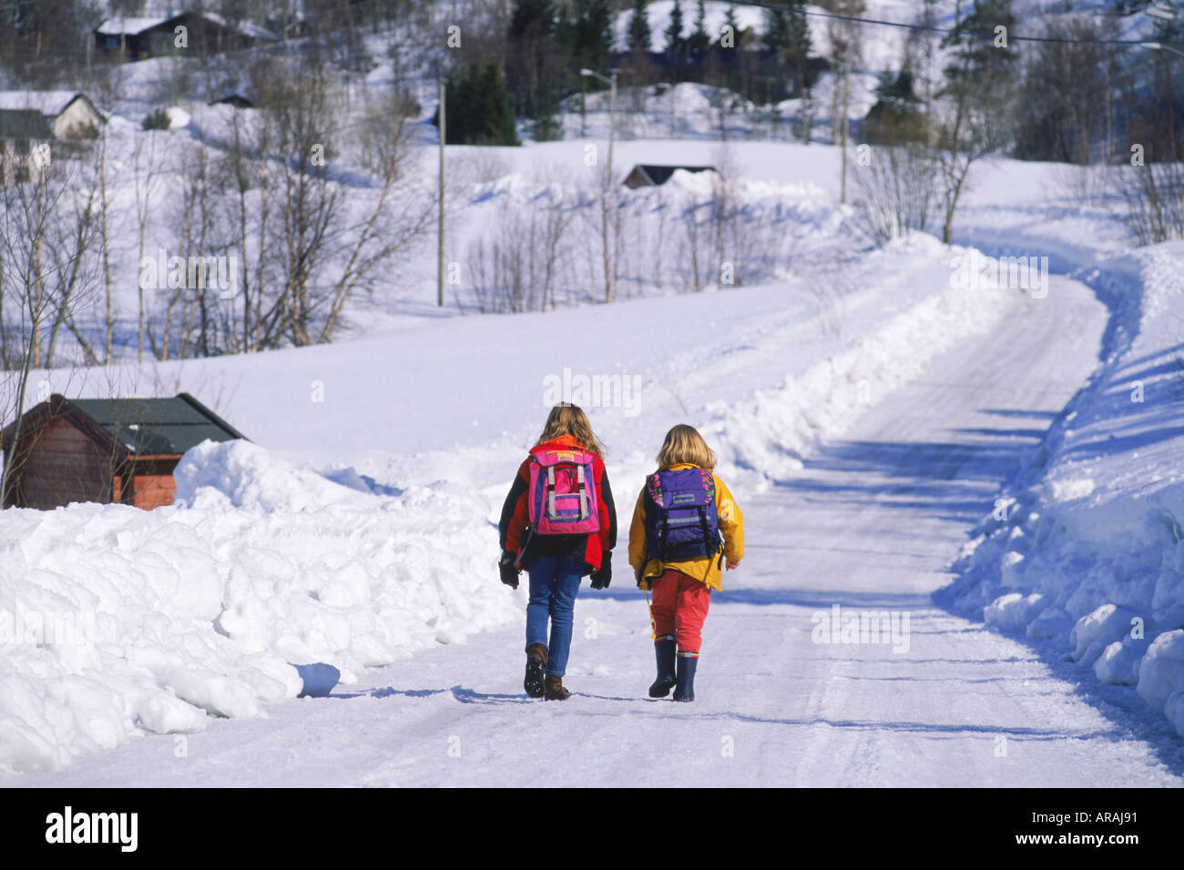 Two School Children With Backpacks On Country Road In Winter In
