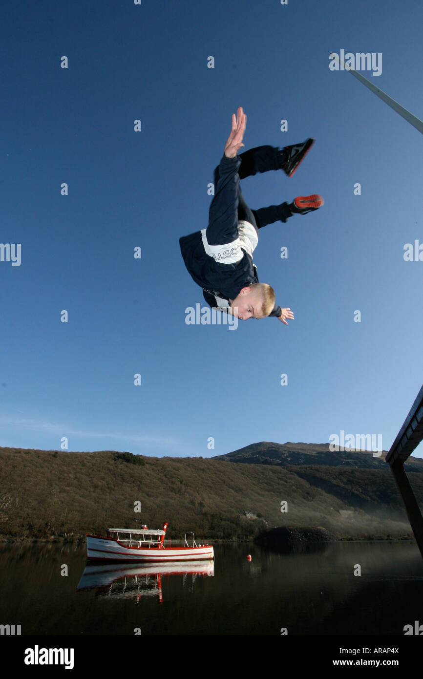 A Parkour Freerunner backflips off a ledge with a boat in the background, taken In Llanberis, North Wales. - Stock Image