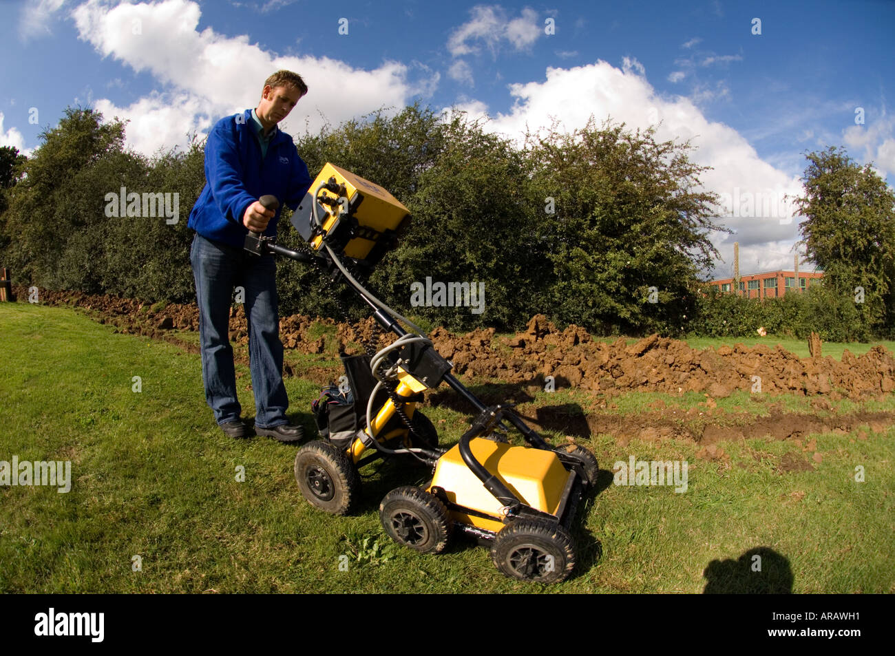 Trained technician operating geophysics machine ground penetrating radar used in forensic cases to locate buried objects - Stock Image