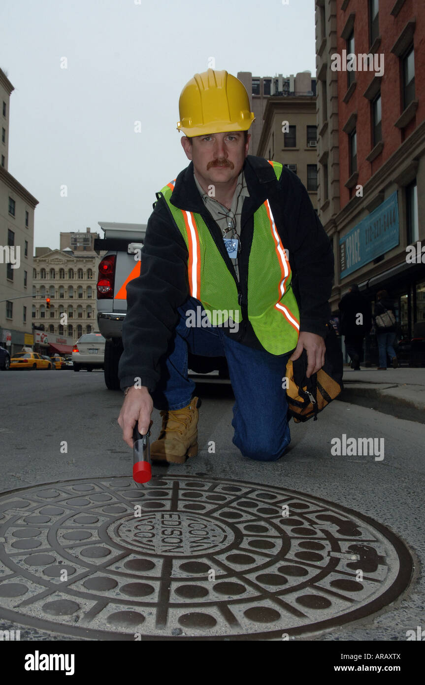 Employee of Con Edison power company in NYC uses a sensor to measure for dangerous stray voltage on a manhole cover - Stock Image