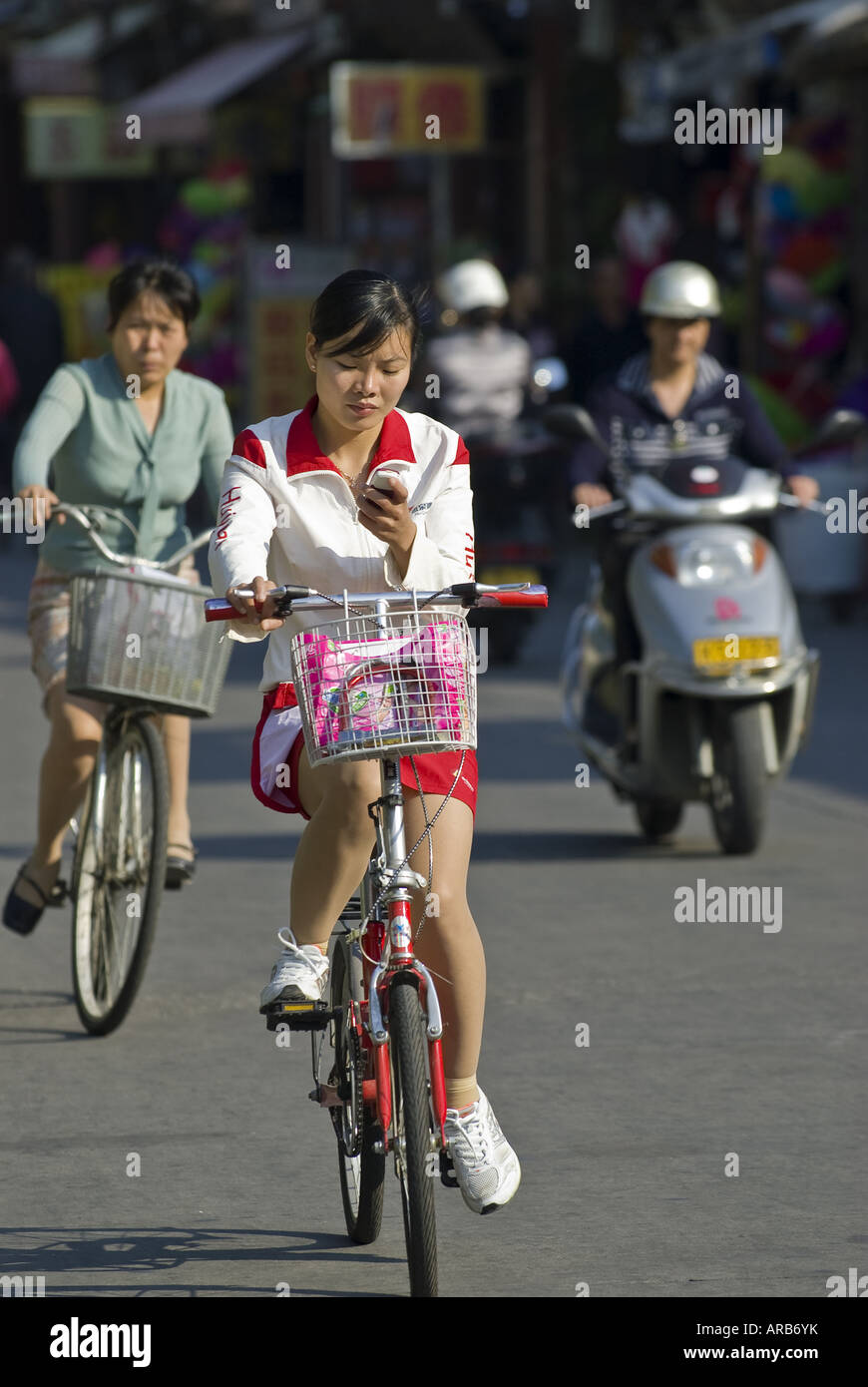Young woman bicycles and text messages, Quanzhou, Fujian Province, China - Stock Image