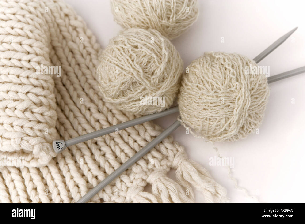 Knitting needles, wool and a plain knit cream scarf - Stock Image