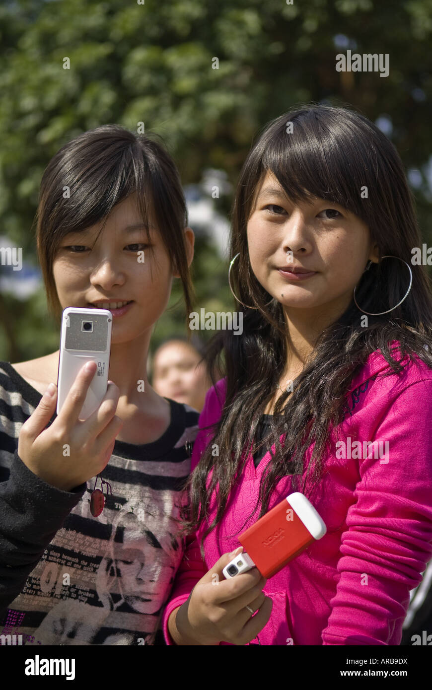 Young women with cellular phones text message, Quanzhou, Fujian Province, China - Stock Image