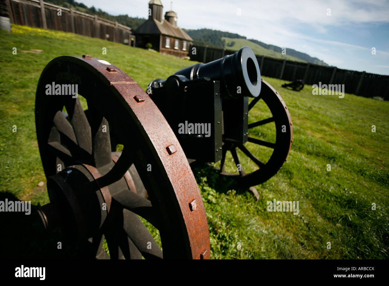 Antique canon inside a fort on green grass with building in the background - Stock Image
