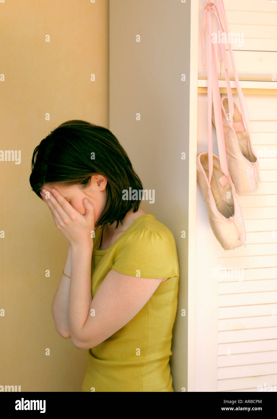 Sad unhappy teen girl in her bedroom with her hands over her face - Stock Image