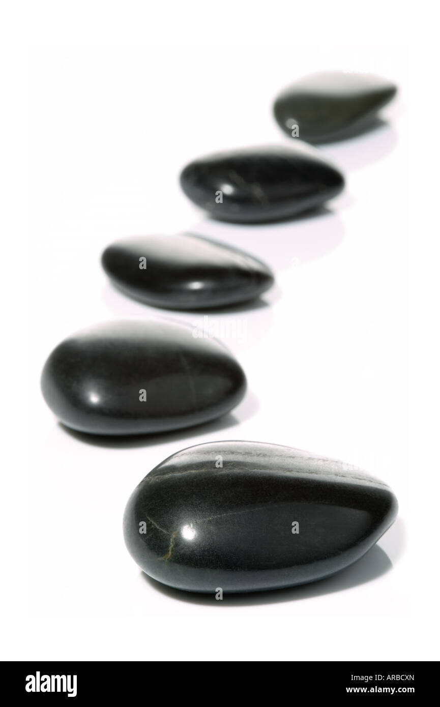 Five black pebbles in a gentle curve on a white surface with reflection High key shot with shallow depth of field - Stock Image
