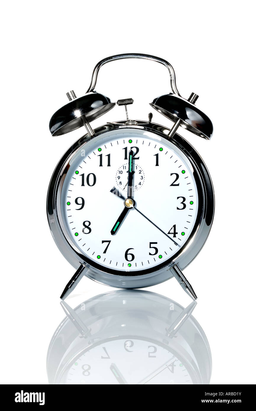A chrome alarm clock with the hands at 7 o clock - Stock Image