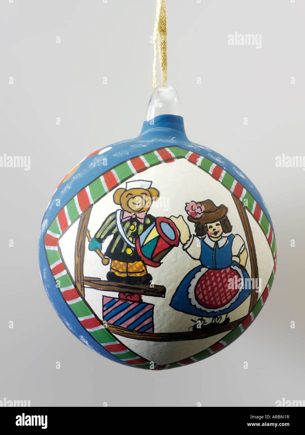 Traditional festive hand painted Christmas  decoration with toy bear and doll in blue and white and green - Stock Image