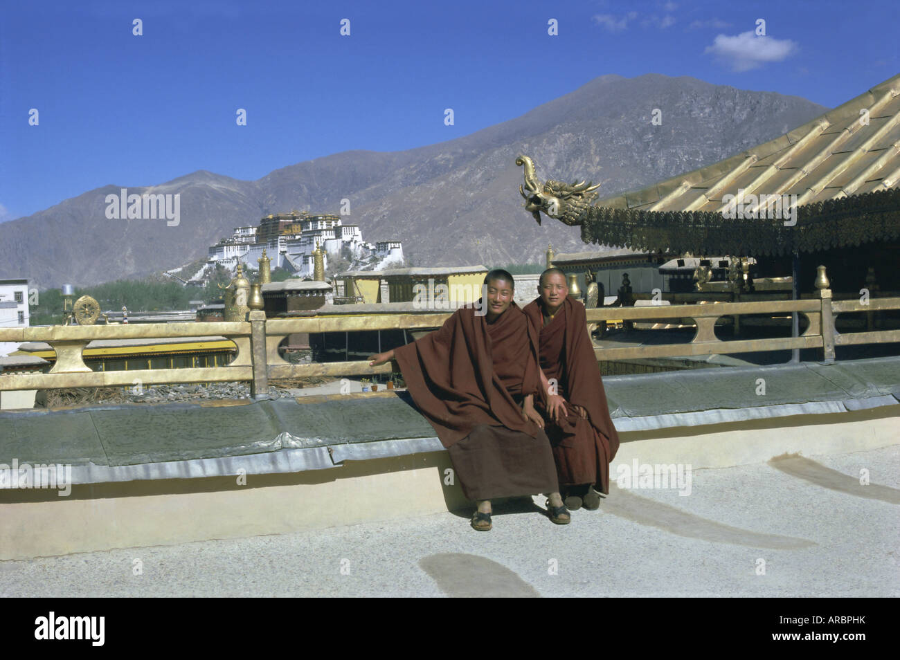 Two Tibetan Buddhist monks at Jokhang temple, with the Potala palace behind, Lhasa, Tibet, China, Asia - Stock Image