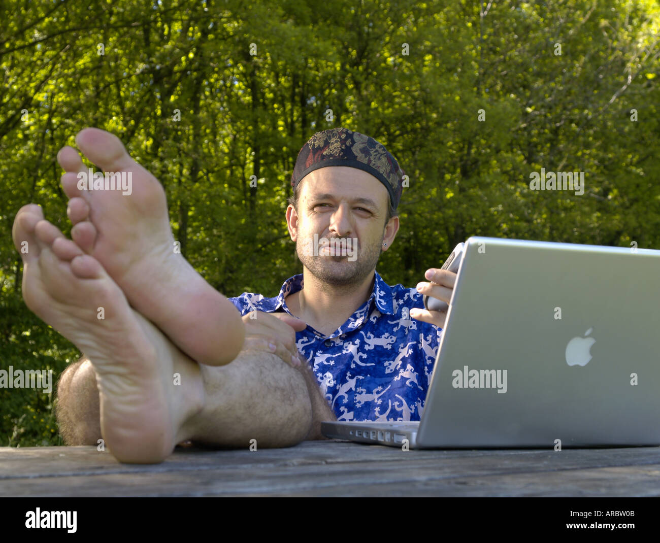 Man with blue shirt and notebook outdoors Stock Photo