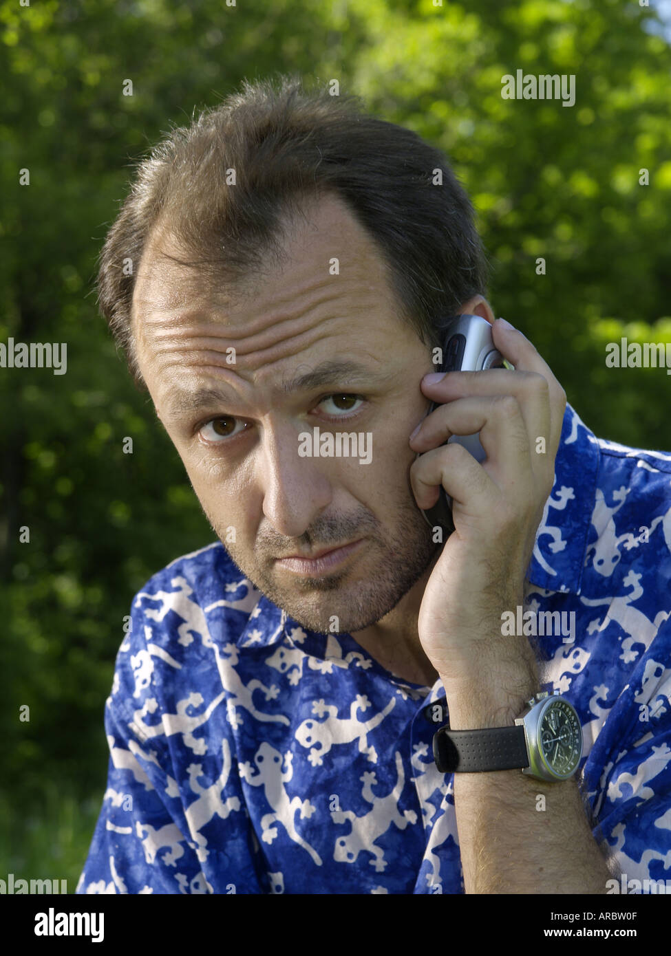 Man with blue shirt and mobile phone outdoors Stock Photo