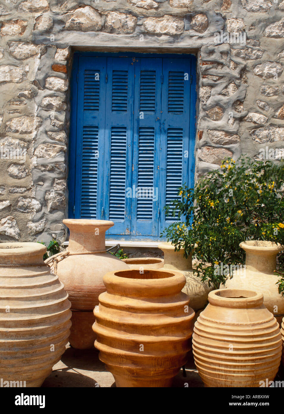 Greek urns in front of a blue door on Hydra, Argo Saronic Islands, Greece - Stock Image
